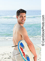 Handsome man beside the sea with his surfboard