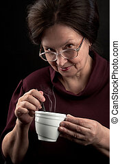 Smiling woman with cup of hot drink - Smiling woman in...
