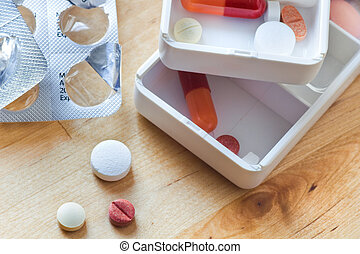 Tablets, capsules and pills sorted in pillboxes for daily...