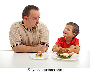 Man and young boy rival over food