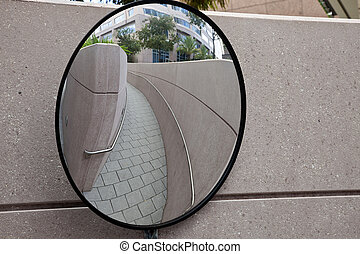 Mirror on the corner between corridors in busy bussines area