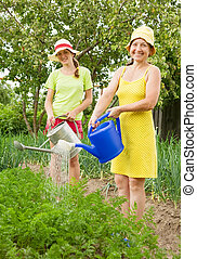 Women watering with watering pot - Two Women watering...