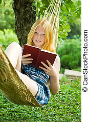girl reading book on hammoc - young girl reading book on...