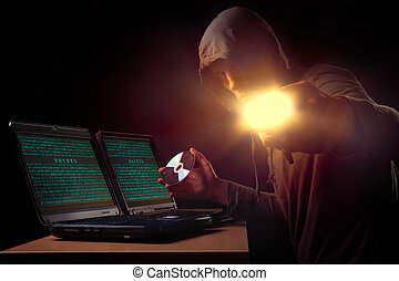 Thief - Hacker in front of two laptops in dark atmosphere....
