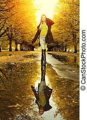 Woman at autumn walking on puddle