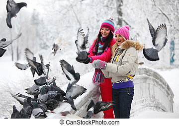 Feeding Pigeons - winter women give food to the pigeon