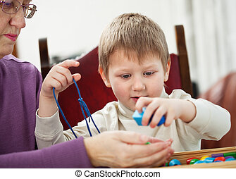 Granny and grandson - Granny is playing with her grandson at...
