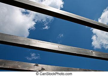 Blue sky through wooden beams.