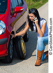 Woman with a flat tire in car - Young woman with a flat tire...