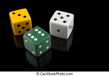 Green, yellow and white dices on black background