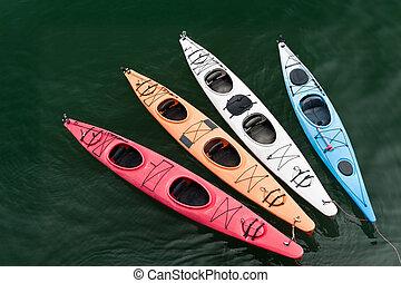 Tethered Kayaks - Four colorful fiberglass kayaks on a...