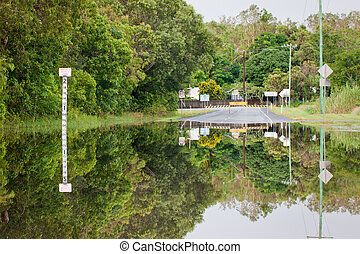Flooded road with depth indicators - A flooded road with...