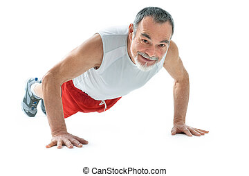 fitness - senior man doing push-ups exercise in gym.