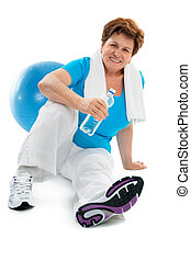 fitness - senior woman sitting in gym and holding water...