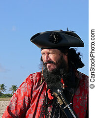 A Black Bearded Pirate in Vintage Costume Looks out the Sea from the beach on a beautiful sunny day.