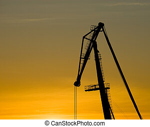 Crane silhouette over sunset sky