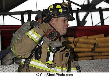Firefighter holding hose across shoulder