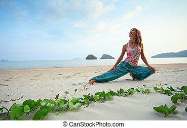 Woman - Young smiling woman doing exercises on sand on blue...