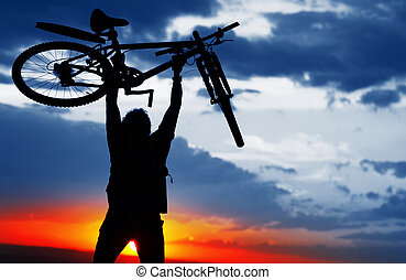 Bike - Man holding a bicycle over himself on sunset...