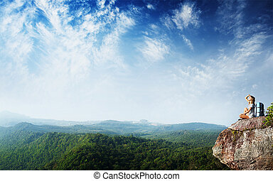 Backpacker - Young woman with backpack sitting on cliff's...