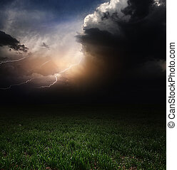 Storm - Dark storm clouds with flashes over meadow with...