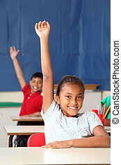 Two school children arms raised - Two happy young primary...