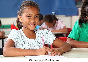 Schoolgirl in classroom writing - Young primary school girl,...