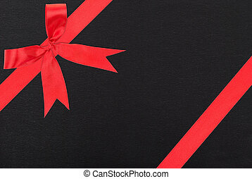 Red satin ribbon and bow gift box wrapping over black paper background