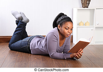 Beautiful girl at home on the floor reading a book -...