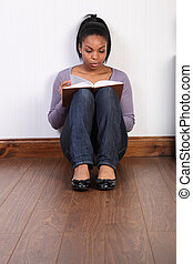 Young black girl concentrating hard reading a book
