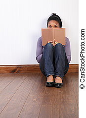 Black girl sitting on floor at home reading book