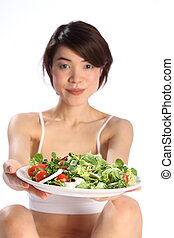 Happy girl and plate of green salad