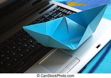 Paper boat sailing on laptop - Blue paper boat sailing on...