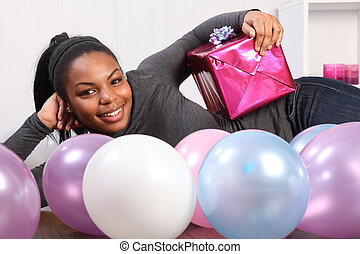 Young girl party time with present and balloons