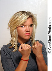 Attractive Young Blonde with Fists Clenched - A studio...