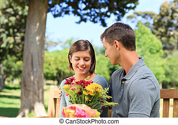 Young man offering flowers to his girlfriend