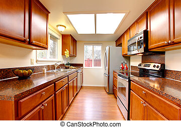 Kitchen warm maple color with stainless steal appliances