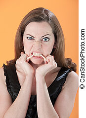 Angry Young Woman - Angry young Caucasian woman biting her...