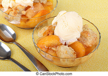Peach Cobbler Dessert - Two bowls of peach cobbler with ice...