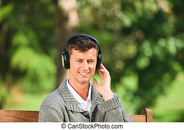 Young man listening to some music on the bench