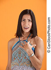 Baffled Woman - Young Latina on an orange background looks...