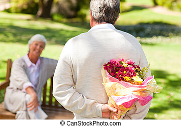 Retired man offering flowers to his wife