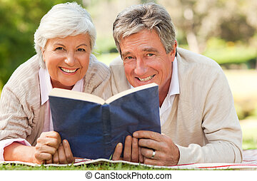 Couple reading a book in the park