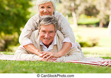 Mature couple lying down in the park