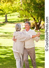 Mature couple dancing in the park