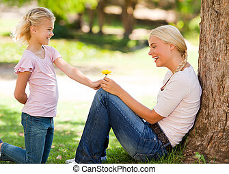 Daughter offering a flower to her m