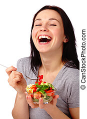 Young attractive woman eats vegetable salad using fork,...