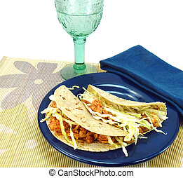 Two fish tacos made with corn tortillas, fish, and cabbage...