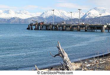 an industrial pier extending out into Kachemak Bay on the Homer  Spit in Alaska with the snow covered Kenai Mountains in the background