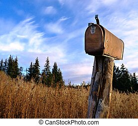 A rusty old rural mailbox on a wooden post in dry grass with...
